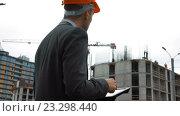 Купить «Архитектор с планшетом перед строящемся зданием», видеоролик № 23298440, снято 18 июля 2016 г. (c) Алексей Собченко / Фотобанк Лори