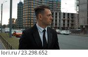 Купить «Бизнесмен в костюме гуляет возле новостроек», видеоролик № 23298652, снято 18 июля 2016 г. (c) Алексей Собченко / Фотобанк Лори