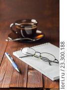Блокнот с ручкой и очками на деревянном столе рядом с чашкой кофе. Стоковое фото, фотограф Александр Якимов / Фотобанк Лори