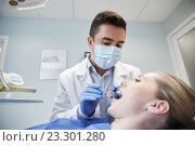 Купить «male dentist in mask checking female patient teeth», фото № 23301280, снято 23 мая 2015 г. (c) Syda Productions / Фотобанк Лори