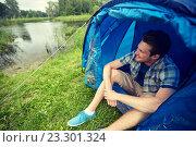 Купить «happy young man sitting in tent at camping», фото № 23301324, снято 25 июля 2015 г. (c) Syda Productions / Фотобанк Лори