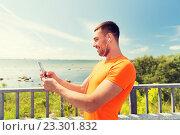 Купить «smiling young man with smartphone and earphones», фото № 23301832, снято 5 июля 2015 г. (c) Syda Productions / Фотобанк Лори
