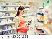 Купить «happy pregnant woman with smartphone at pharmacy», фото № 23301884, снято 27 июля 2015 г. (c) Syda Productions / Фотобанк Лори