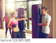 Купить «smiling woman with personal trainer boxing in gym», фото № 23301920, снято 29 июня 2014 г. (c) Syda Productions / Фотобанк Лори