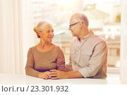 Купить «happy senior couple sitting on sofa at home», фото № 23301932, снято 4 сентября 2014 г. (c) Syda Productions / Фотобанк Лори