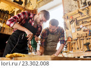 Купить «carpenters with drill drilling plank at workshop», фото № 23302008, снято 14 мая 2016 г. (c) Syda Productions / Фотобанк Лори