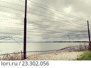 Купить «barb wire fence over gray sky and sea», фото № 23302056, снято 30 сентября 2015 г. (c) Syda Productions / Фотобанк Лори