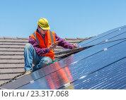 Купить «Рабочий устанавливает панели солнечных батарей», фото № 23317068, снято 26 декабря 2014 г. (c) Кропотов Лев / Фотобанк Лори