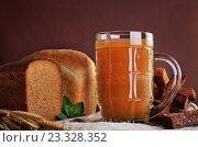 Купить «Кружка кваса и хлеб на коричневом фоне», фото № 23328352, снято 19 апреля 2015 г. (c) Алексей Давидчук / Фотобанк Лори