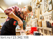 Купить «carpenter with drill drilling plank at workshop», фото № 23342108, снято 14 мая 2016 г. (c) Syda Productions / Фотобанк Лори