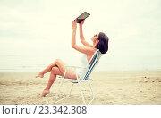 Купить «happy woman with tablet pc taking selfie on beach», фото № 23342308, снято 6 августа 2015 г. (c) Syda Productions / Фотобанк Лори