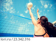 young woman with ball playing volleyball on beach. Стоковое фото, фотограф Syda Productions / Фотобанк Лори