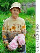 Купить «Пожилая женщина садовод стоит и улыбается рядом с розовыми пионами», фото № 23349560, снято 27 июня 2016 г. (c) Максим Мицун / Фотобанк Лори