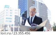 Купить «senior businessman with ring binder folder in city», видеоролик № 23355456, снято 23 июля 2016 г. (c) Syda Productions / Фотобанк Лори