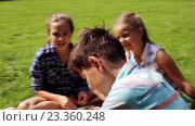 Купить «group of happy kids sitting on grass and talking», видеоролик № 23360248, снято 30 июля 2016 г. (c) Syda Productions / Фотобанк Лори