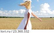 Купить «smiling young woman in white dress on cereal field», видеоролик № 23360332, снято 3 августа 2016 г. (c) Syda Productions / Фотобанк Лори