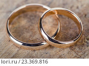 Купить «Two gold wedding rings on wooden background», фото № 23369816, снято 5 мая 2016 г. (c) Elnur / Фотобанк Лори