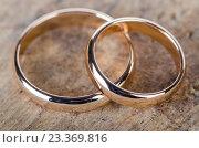 Two gold wedding rings on wooden background. Стоковое фото, фотограф Elnur / Фотобанк Лори