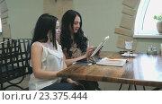 Купить «Две девушки смотрят фотографии на цифровом планшете», видеоролик № 23375444, снято 21 февраля 2016 г. (c) worker / Фотобанк Лори