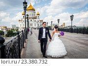Купить «Bride and groom pose on the The Luzhkov Bridge, Wedding Bridge, or Bridge of Kisses, over the Moskva River, Moscow, Russia.», фото № 23380732, снято 13 июля 2013 г. (c) age Fotostock / Фотобанк Лори