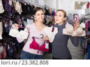 Купить «two female customers holding bras and panties in hands in underwear store», фото № 23382808, снято 30 мая 2020 г. (c) Яков Филимонов / Фотобанк Лори