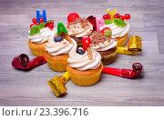 Кексы с ягодами, свечами и праздничными дудками. Стоковое фото, фотограф julia Lebed / Фотобанк Лори