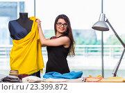 Купить «Woman tailor working on new clothing», фото № 23399872, снято 30 мая 2016 г. (c) Elnur / Фотобанк Лори