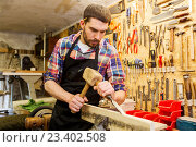 Купить «carpenter with wood, hammer and chisel at workshop», фото № 23402508, снято 14 мая 2016 г. (c) Syda Productions / Фотобанк Лори