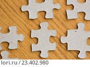 Купить «close up of puzzle pieces on wooden surface», фото № 23402980, снято 21 апреля 2016 г. (c) Syda Productions / Фотобанк Лори