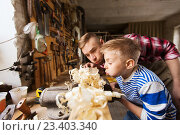 Купить «father and little son with wood plank at workshop», фото № 23403340, снято 14 мая 2016 г. (c) Syda Productions / Фотобанк Лори