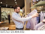 Купить «happy young man choosing clothes in clothing store», фото № 23404032, снято 1 апреля 2016 г. (c) Syda Productions / Фотобанк Лори