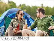 Купить «happy couple drinking beer at campsite tent», фото № 23404408, снято 27 мая 2016 г. (c) Syda Productions / Фотобанк Лори