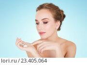 Купить «happy young woman with moisturizing cream on hand», фото № 23405064, снято 14 апреля 2016 г. (c) Syda Productions / Фотобанк Лори