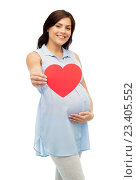 Купить «happy pregnant woman with red heart touching belly», фото № 23405552, снято 20 мая 2016 г. (c) Syda Productions / Фотобанк Лори