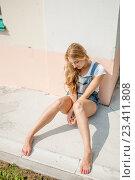 Красивая девушка в летнем джинсовом комбинезоне сидит около стены. Стоковое фото, фотограф Никита Вишневецкий / Фотобанк Лори