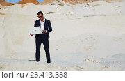 Купить «Молодой красавец в деловом костюме в пустыне эмоционально поднимает руки вверх с ноутбуком. Радость победы. Достижение успеха.», видеоролик № 23413388, снято 16 августа 2016 г. (c) Сергей Мнацаканов / Фотобанк Лори