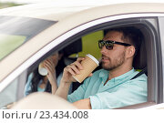 happy man and woman driving in car with coffee. Стоковое фото, фотограф Syda Productions / Фотобанк Лори