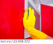 Женщина протирает влажной губкой кухонный шкаф. Стоковое фото, фотограф Сергей Макаров / Фотобанк Лори