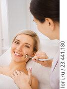 Купить «Веселая девушка на приеме у косметолога. Аппаратная процедура», фото № 23441180, снято 4 августа 2016 г. (c) Mark Agnor / Фотобанк Лори