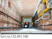 Купить «machinists adjusting lift in elevator hoist way», фото № 23451140, снято 3 февраля 2016 г. (c) Дмитрий Калиновский / Фотобанк Лори
