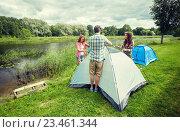 Купить «group of smiling friends setting up tent outdoors», фото № 23461344, снято 25 июля 2015 г. (c) Syda Productions / Фотобанк Лори