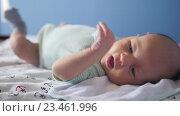 Грудной ребёнок лежит в кроватки и двигает руками и ногами. Стоковое видео, видеограф Павел Котельников / Фотобанк Лори