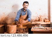 Купить «artisan man creating ceramic piece on spinning pottery wheel in workshop», фото № 23486496, снято 14 июля 2020 г. (c) Яков Филимонов / Фотобанк Лори