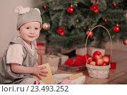 Купить «Little child in festive suit of mouse sits in sledges near the Christmas tree», фото № 23493252, снято 20 декабря 2015 г. (c) Майя Крученкова / Фотобанк Лори