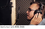 Купить «man with headphones singing at recording studio», видеоролик № 23498944, снято 25 августа 2016 г. (c) Syda Productions / Фотобанк Лори