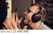 Купить «man with headphones singing at recording studio», видеоролик № 23498948, снято 25 августа 2016 г. (c) Syda Productions / Фотобанк Лори