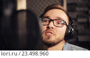 Купить «man with headphones singing at recording studio», видеоролик № 23498960, снято 25 августа 2016 г. (c) Syda Productions / Фотобанк Лори