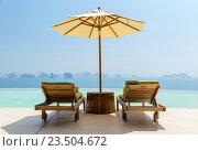 Купить «infinity pool with parasol and sun beds at seaside», фото № 23504672, снято 15 февраля 2015 г. (c) Syda Productions / Фотобанк Лори