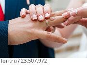 Купить «Невеста надевает золотое свадебное кольцо на палец жениху в ЗАГСе», эксклюзивное фото № 23507972, снято 16 июля 2016 г. (c) Игорь Низов / Фотобанк Лори