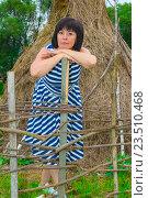 Купить «Женщина стоит у плетня возле стога сена», фото № 23510468, снято 13 августа 2016 г. (c) Дмитрий Брусков / Фотобанк Лори